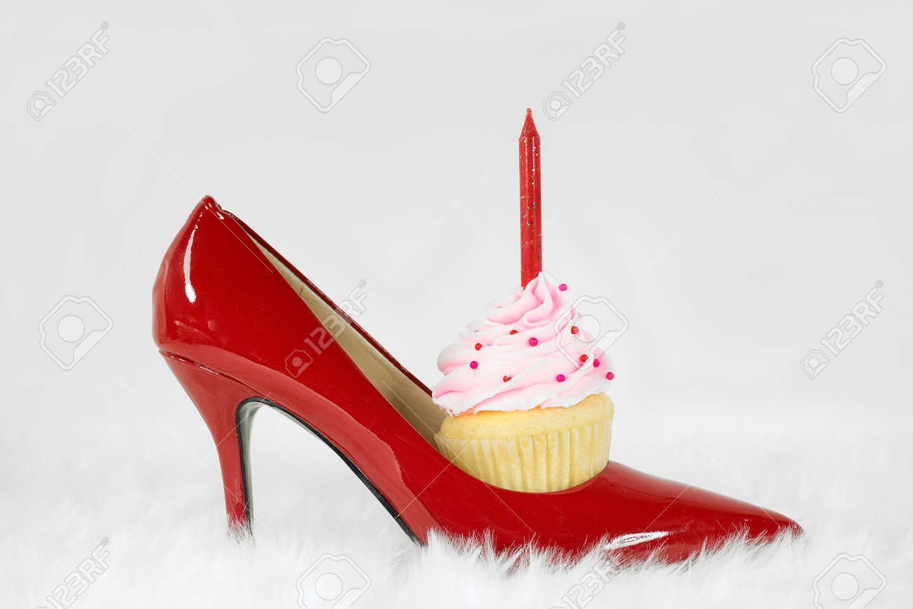 Red High Heel Shoe With Birthday Cupcake On White Fur Stock Photo