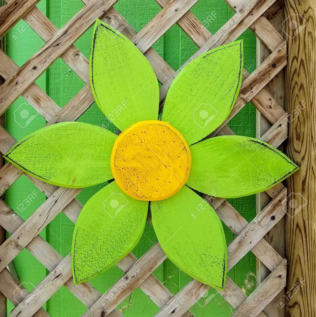 Bright Green Wooden Daisy Decoration On Garden Trellis Stock Photo