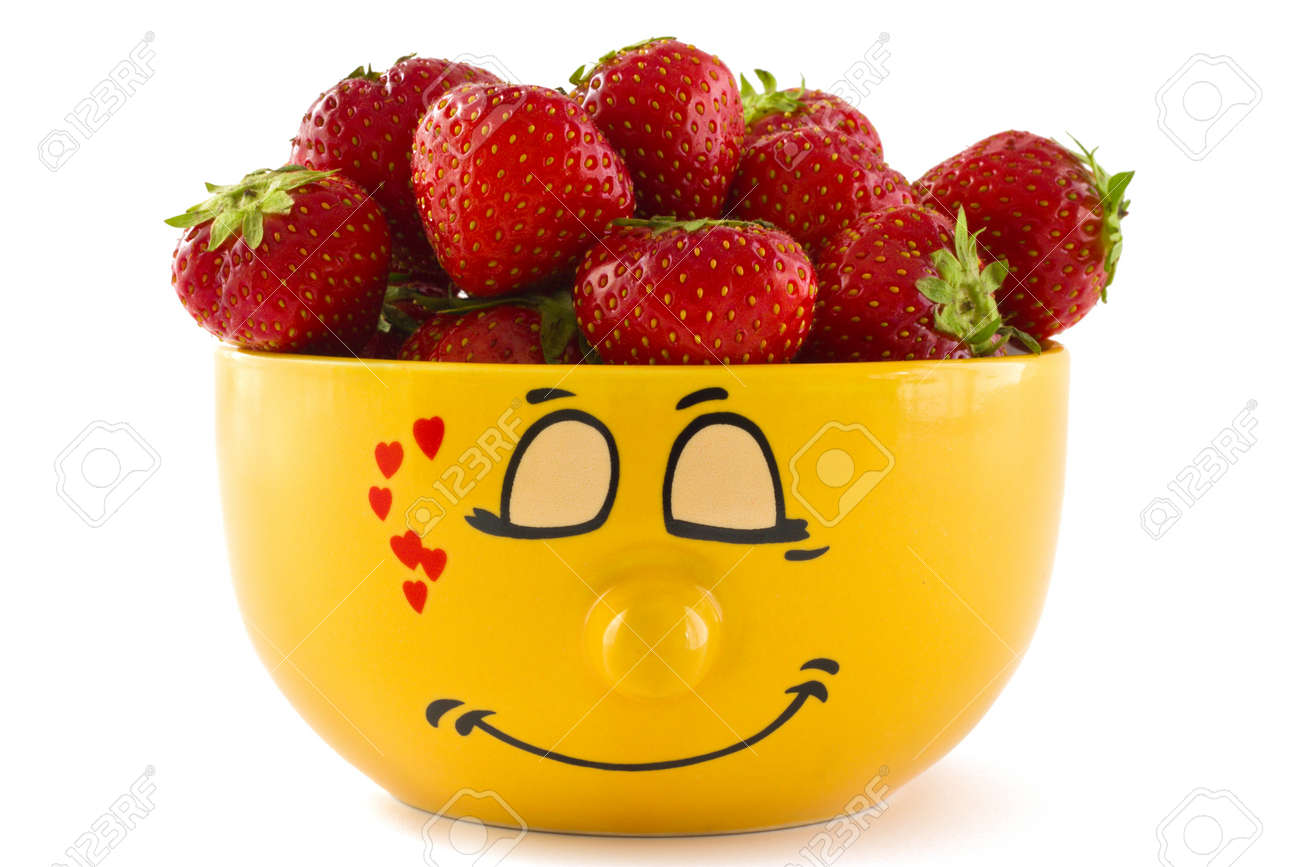 Large yellow cup with a shy face print full of ripe strawberries, isolated on a white background. Stock Photo - 9828176