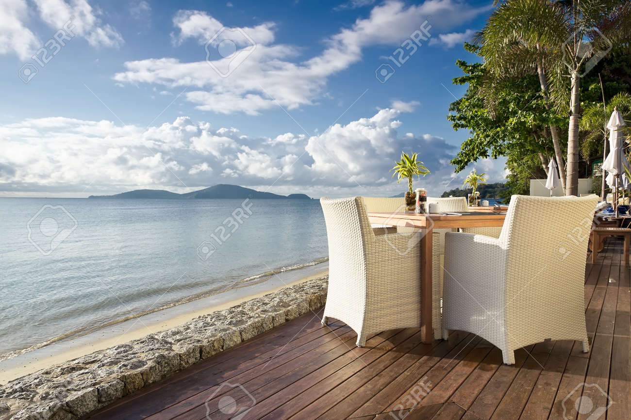 White table with chairs on decking, by the beach Stock Photo - 14386957