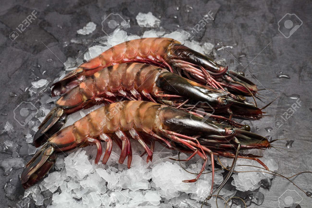 Three Raw Jumbo Shrimps On Ice On Dark Background Stock Photo