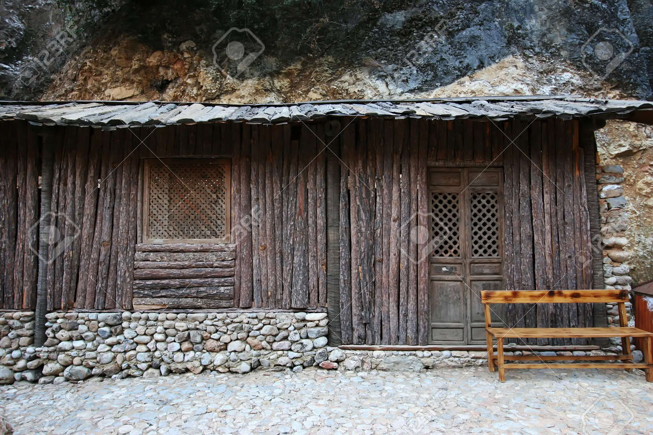 A Wooden House With Stone Foundation And A Wooden Bench In Front Stock  Photo   714111