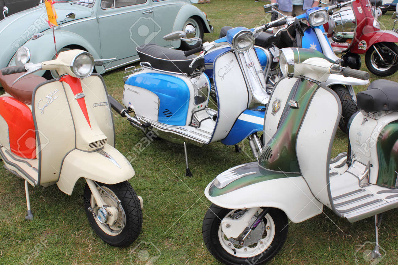A collection of retro scooters with an old retro car in the background at a show in england ,12th august 2012 Stock Photo - 17393098