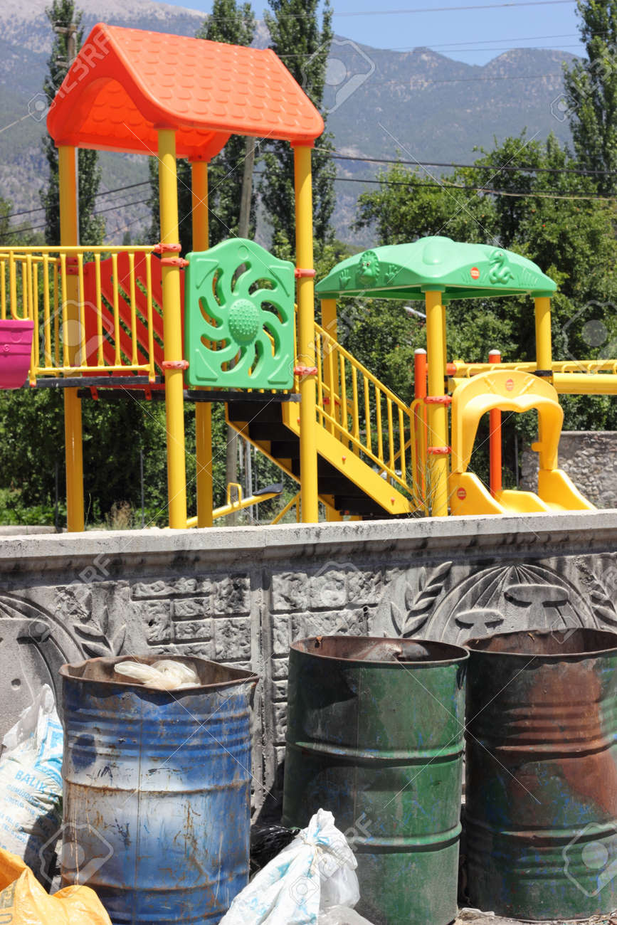 A childrens playground with dangerous waste containers nearby