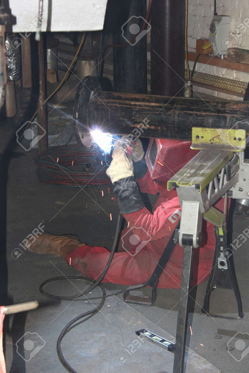 A welder welding a flange onto a pipe for a repair on a steam