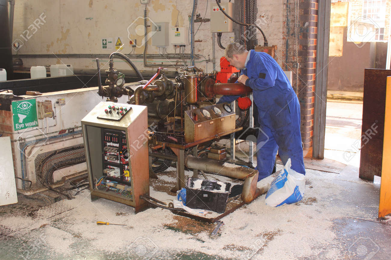 a diesel fuel spill in a boilerhouse being cleaned by an engineer wearing his ppe using