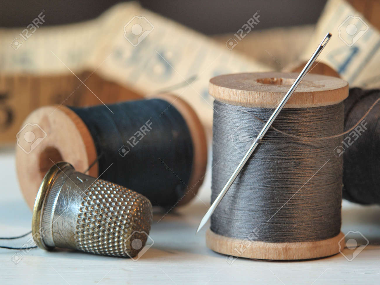 Close up of thread spools, needle, and thimble with a tape measure in the background. Stock Photo - 8208466