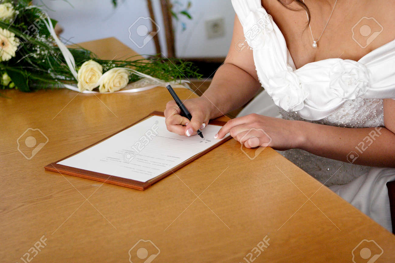 Bride signs the marriage contract Stock Photo - 27721641