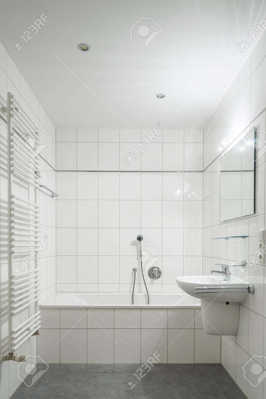 Cuarto de baño de azulejos blancos con inodoro, bañera, lavabo y espejo