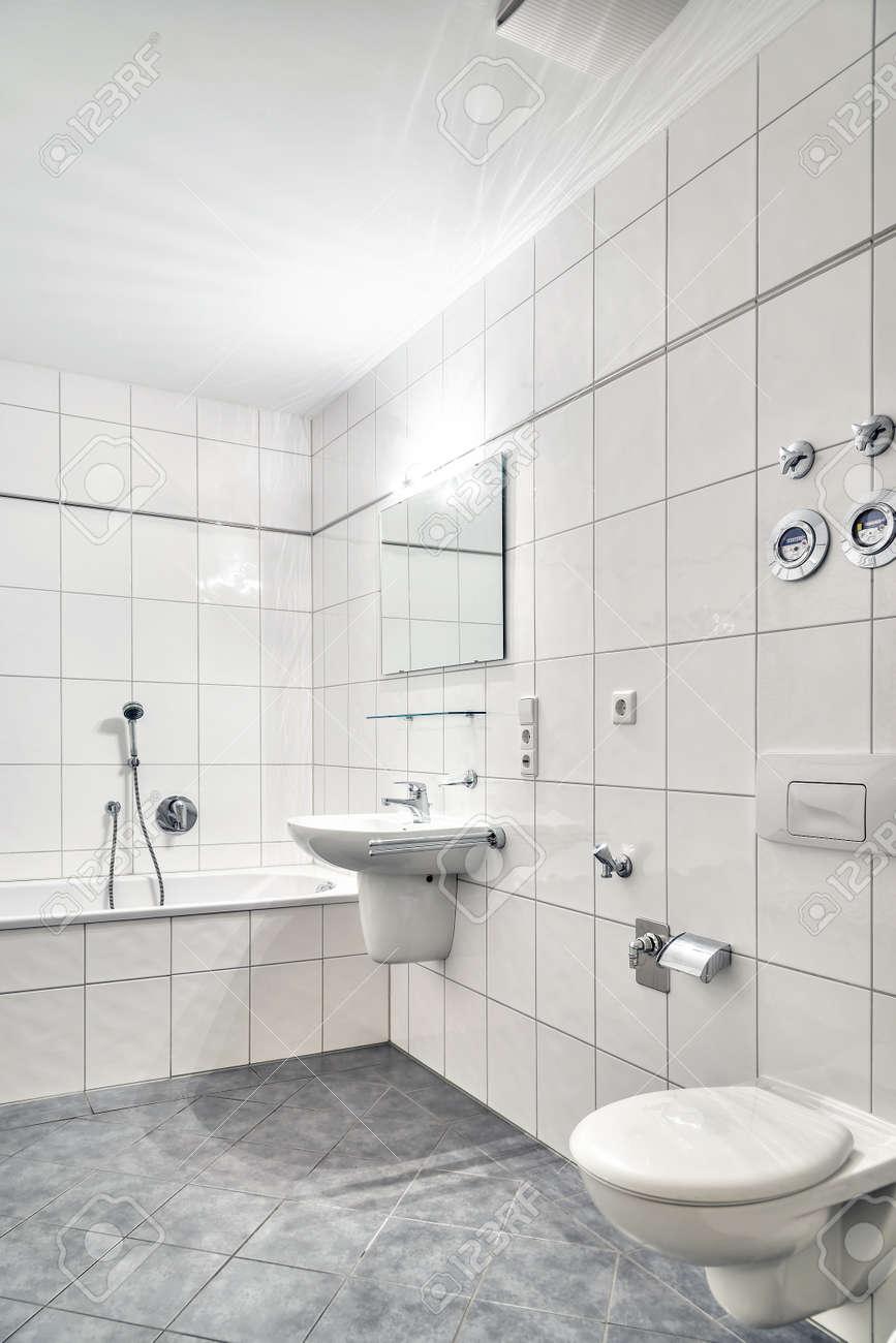 Cuarto de baño de azulejos blancos con lavabo, bañera, WC y espejo