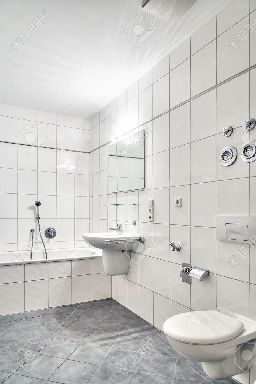 White Tiled Bathroom With Lavatory, Tub, Toilet And Mirror Stock ...