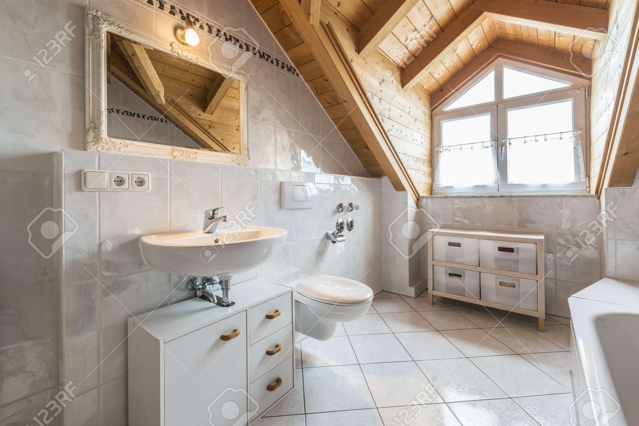 archivio fotografico bagno di un appartamento in mansarda con lavandino specchio luce finestra wc vasca da bagno armadi in legno e soffitto