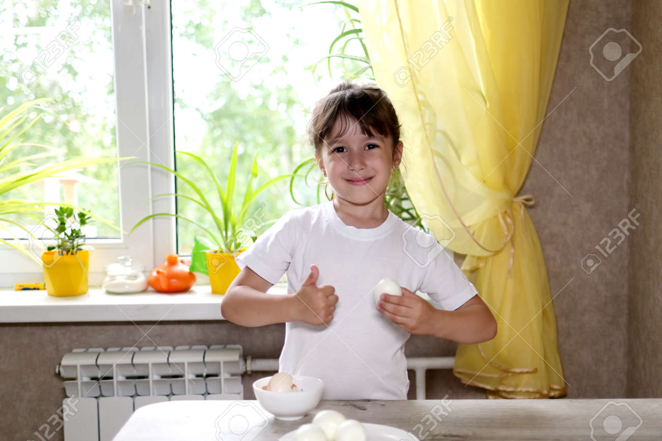 lifestyle preschooler child girl cook food in the kitchen. development of fine motor skills in everyday life from scrap materials. child cleans eggs - 171129141