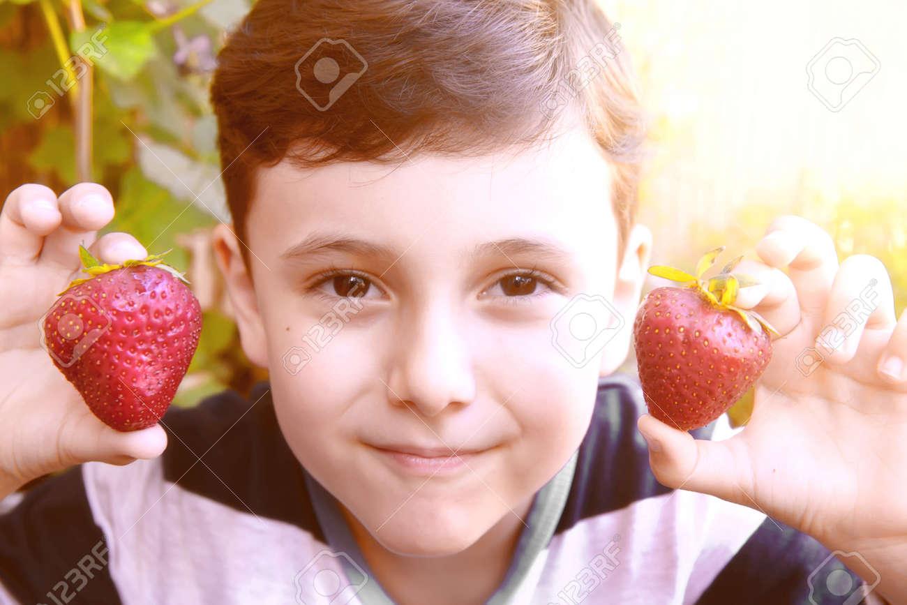 新鮮なイチゴを保持しているかわいい男の子。かわいい男の子の子供食べて