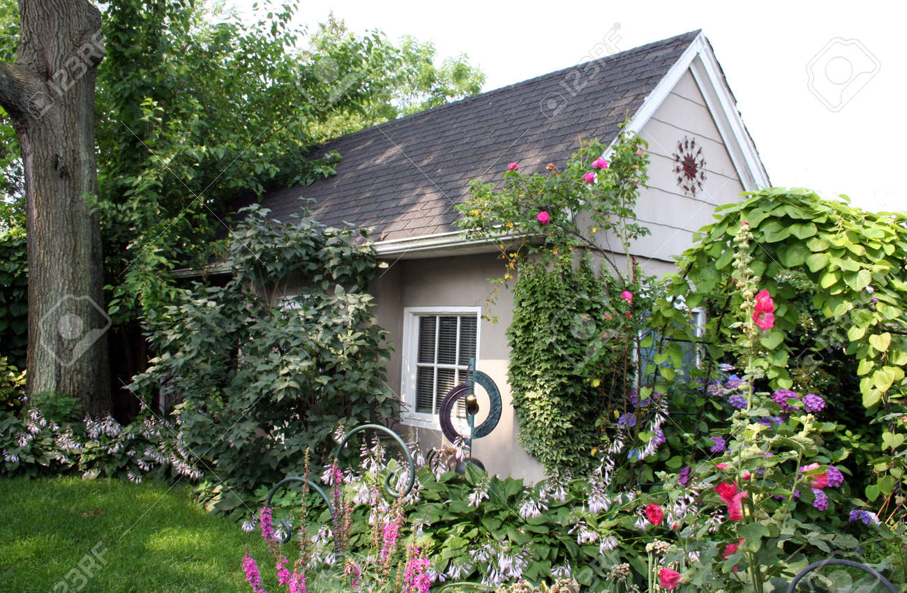 Small Cottage In Beautiful Garden Stock Photo