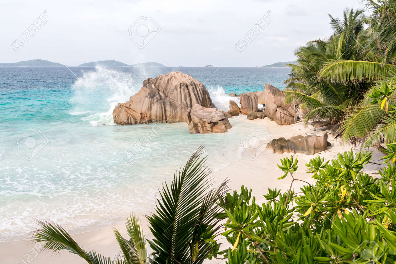 Beach with blue water and blue sky and white sand and some rocks - 117304975