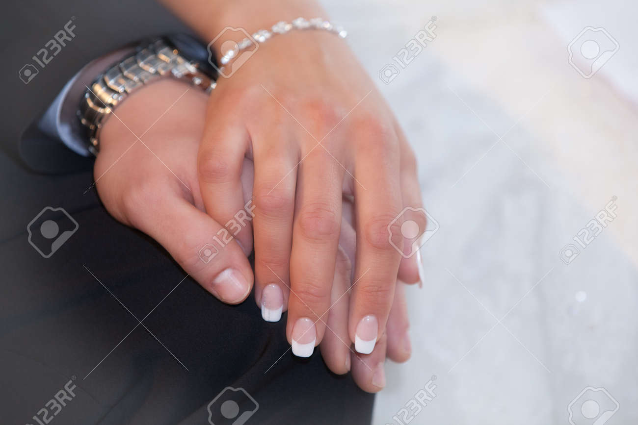 Bride and groom hold their hands romantically - 141299968