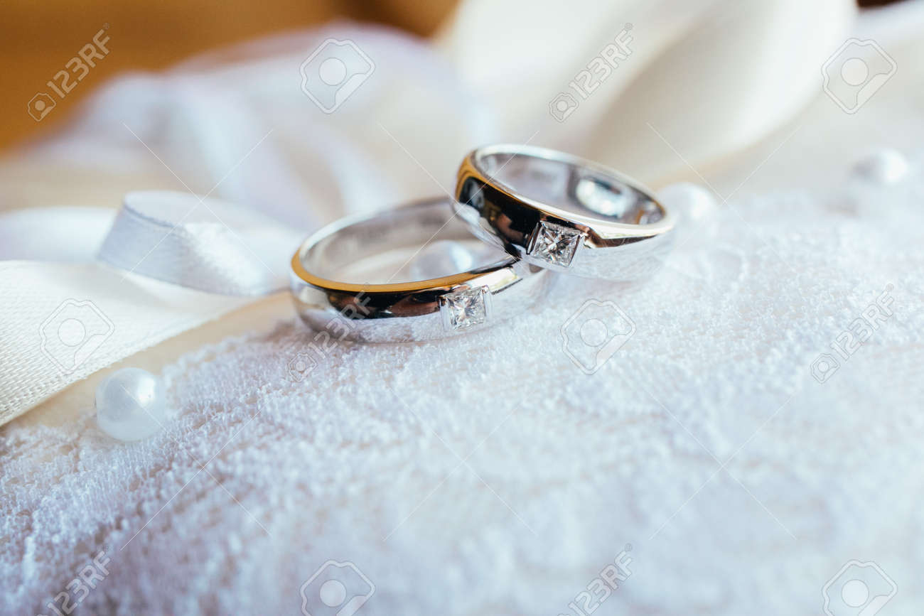 Beautifull wedding rings on white lace pillow - 52838421