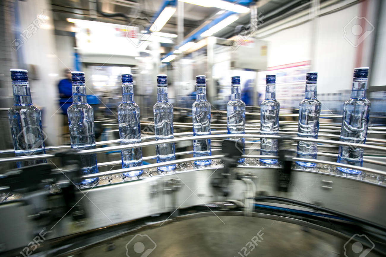 Many bottles on conveyor belt in factory, production of russian traditional alcohol drink vodka - 53136682