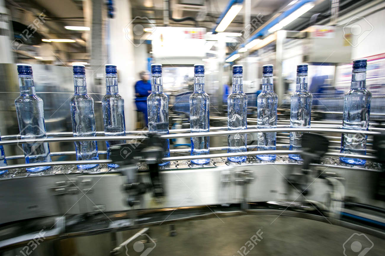 Many bottles on conveyor belt in factory, production of russian traditional alcohol drink vodka - 53136684