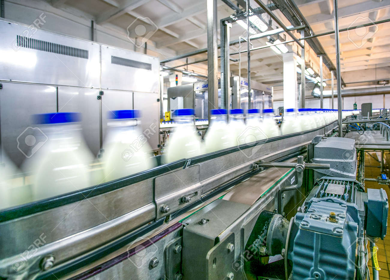 Milk production on line at the factory bottles with milk product in motion focused on conveyer details - 53401428
