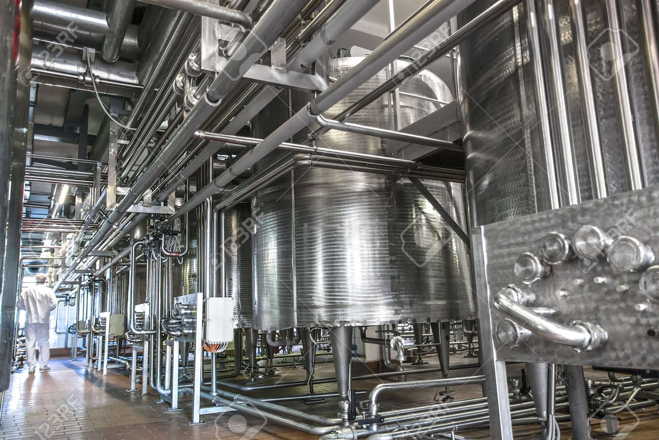 Dairy product factory inside with pipes and tanks - 53401244