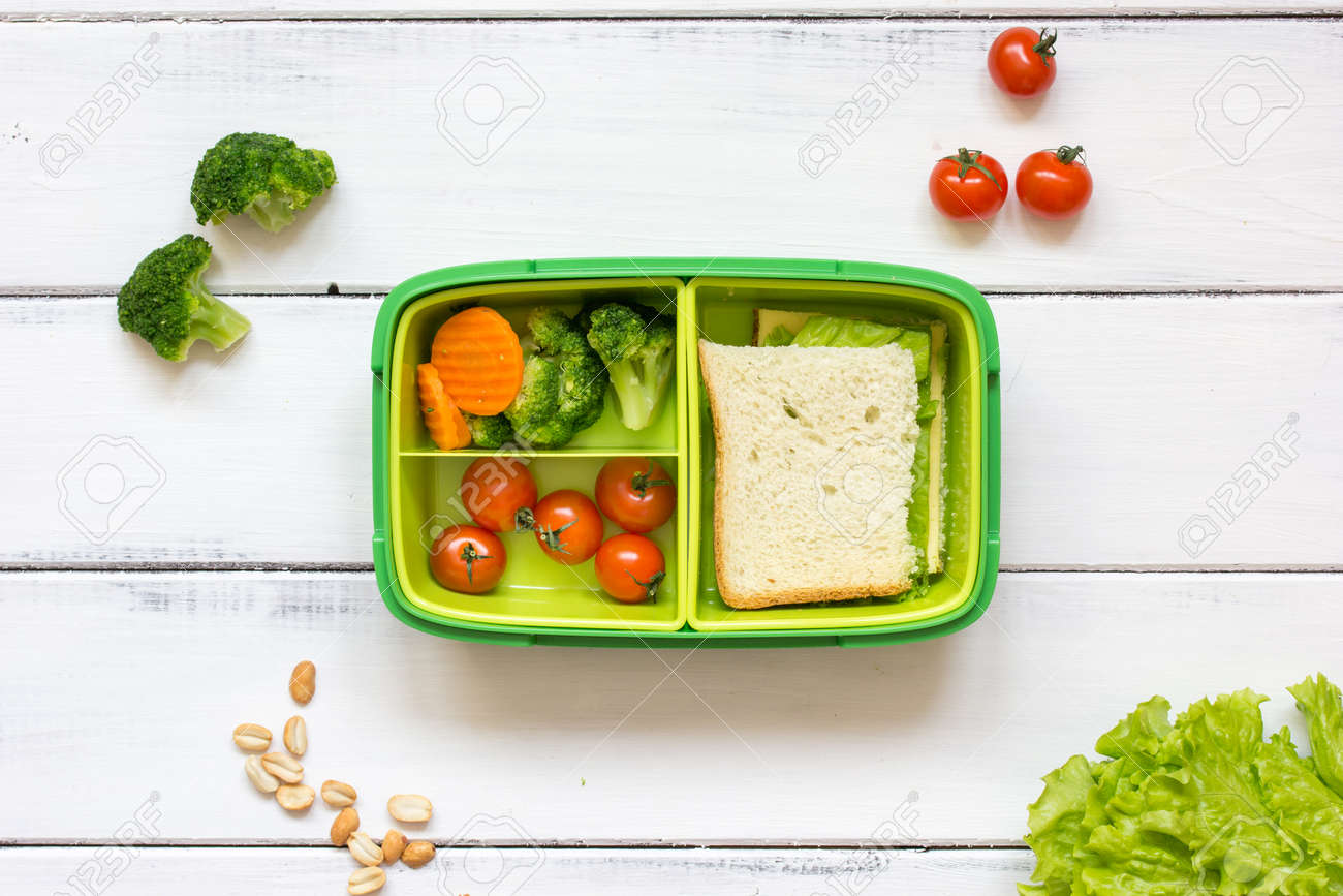 preparing lunch for child with vegetables and fruit to school top view on wooden background - 65396793