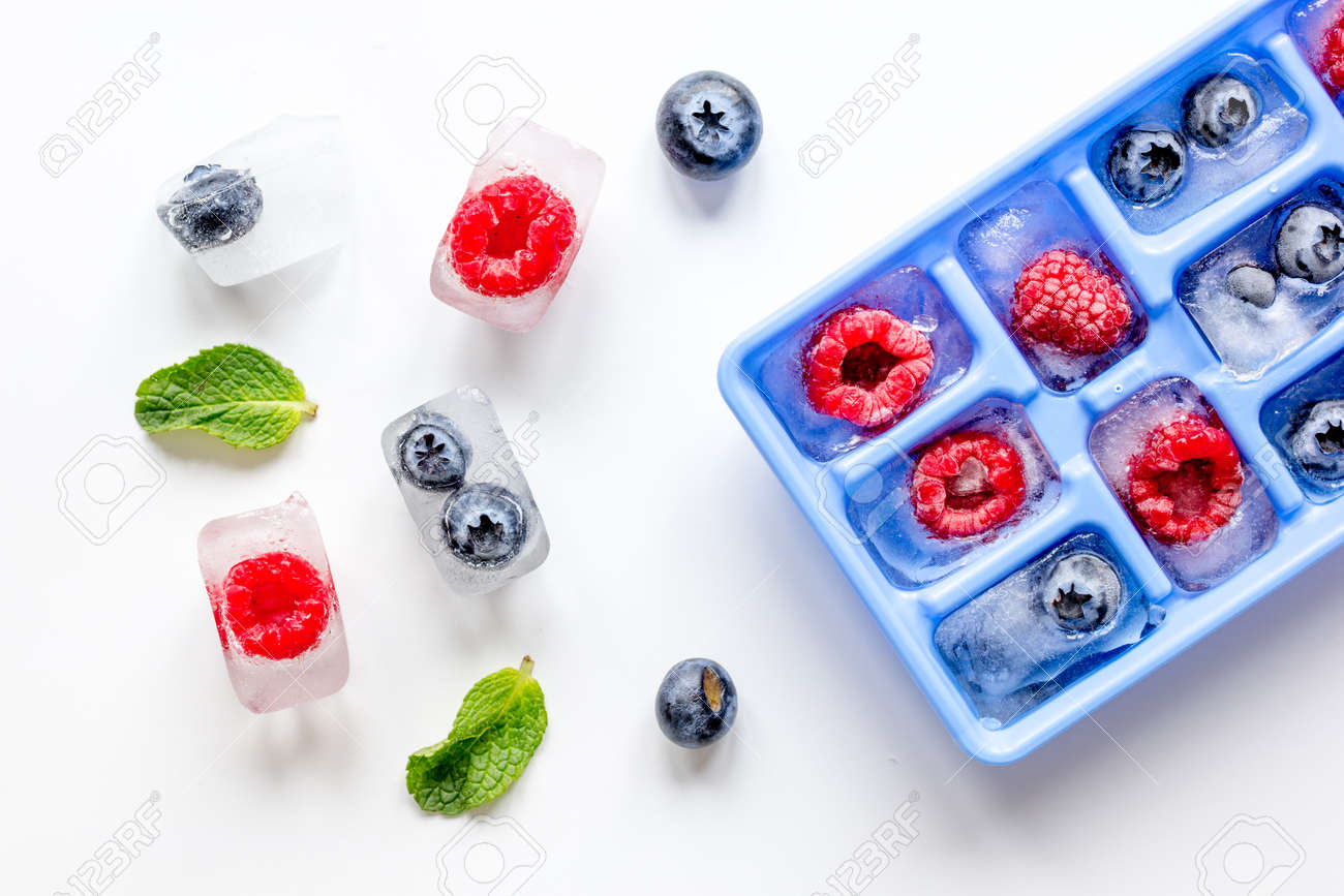 blueberry and raspberry in icetray on stone background top view - 72130709