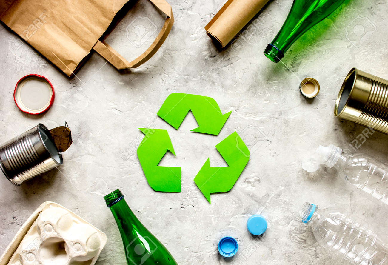 waste recycling symbol with garbage on stone background top view - 73356524