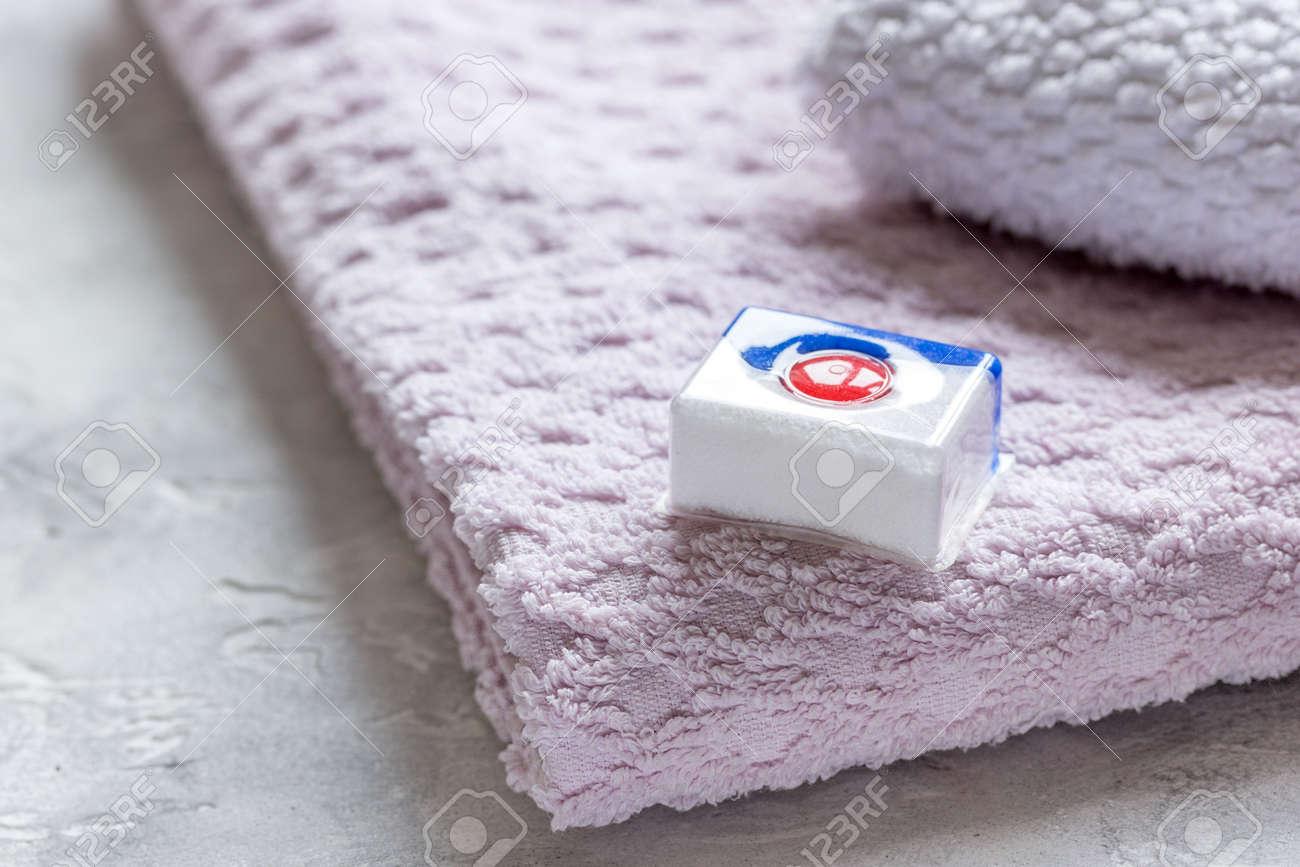 Pila di asciugamani da bagno con detergente in sfondo di lavanderia