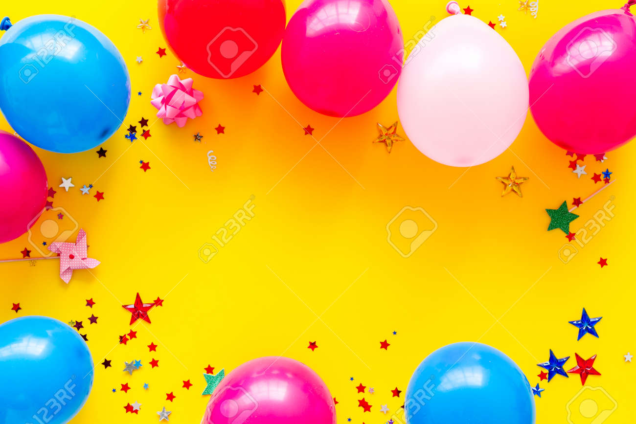 Party concept. Colorful balloons and confetti on yellow background top-down frame copy space - 142716017