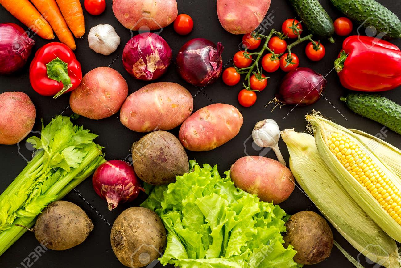 Fresh vegetables still life. Potato, cucumber, beet carrot, greenery on black background top-down - 142864968