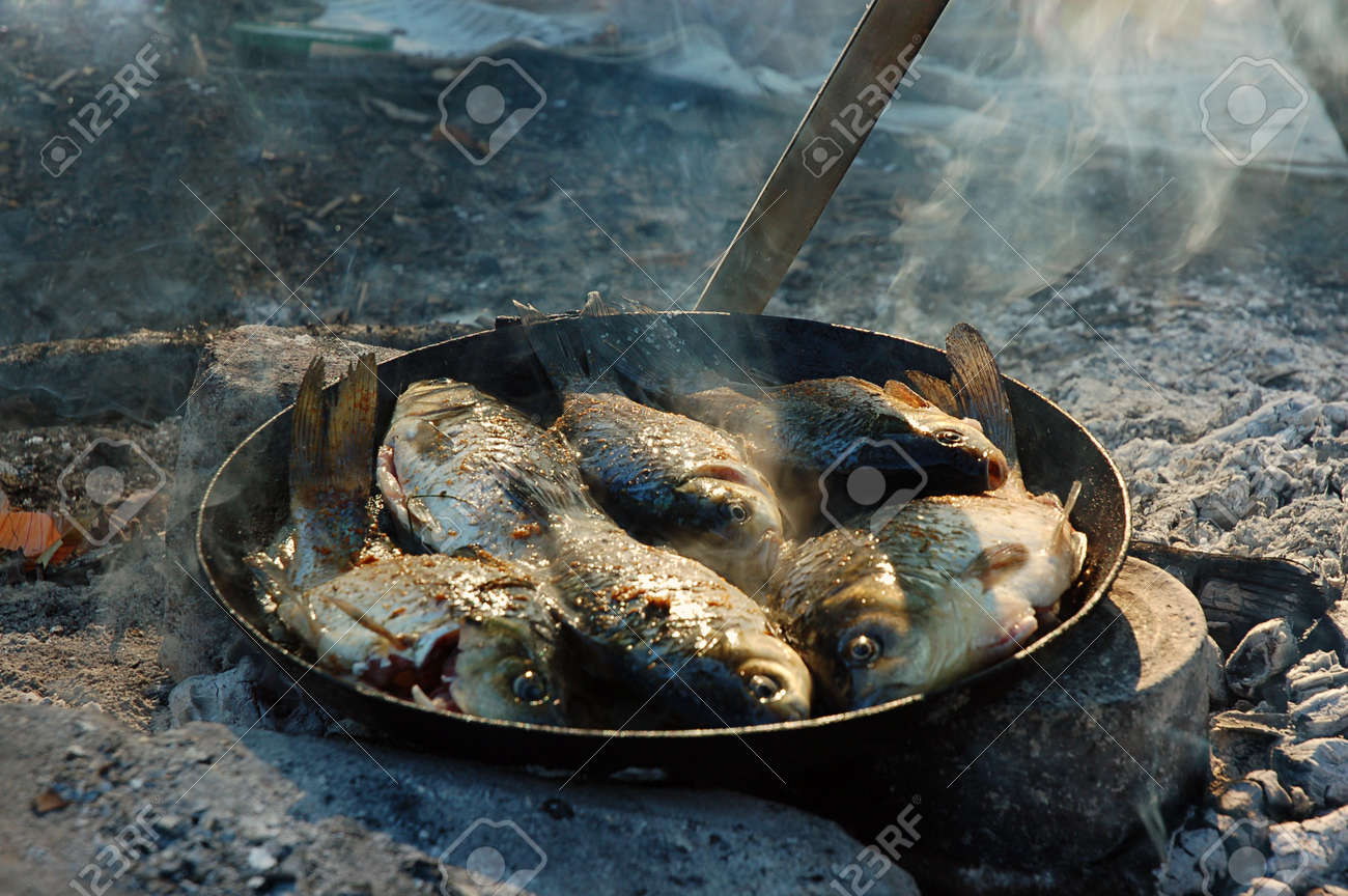 Pan Fried Fresh Fish Cooked Over A Campfire In Campaign Stock Photo
