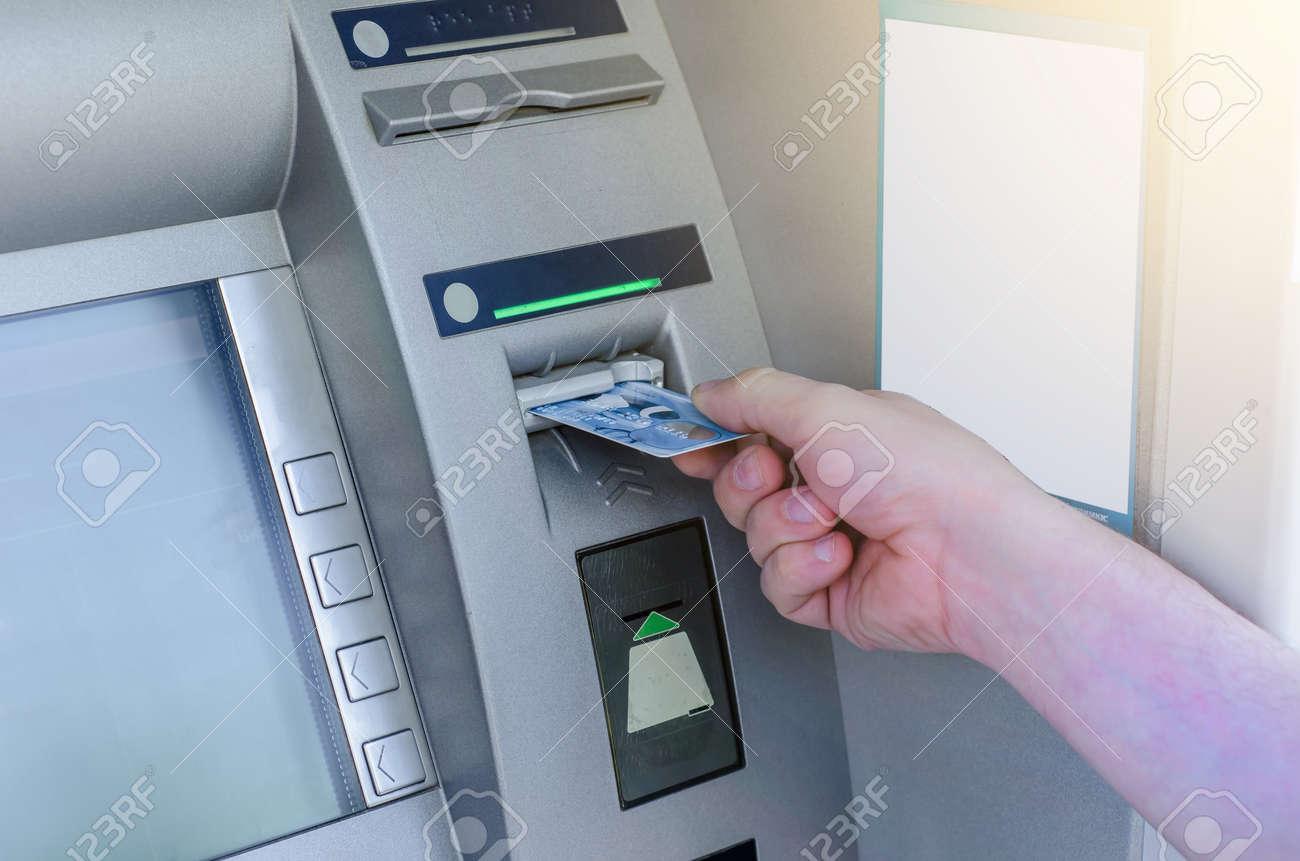 Man hand puts card, press button gray ATM - 150627380