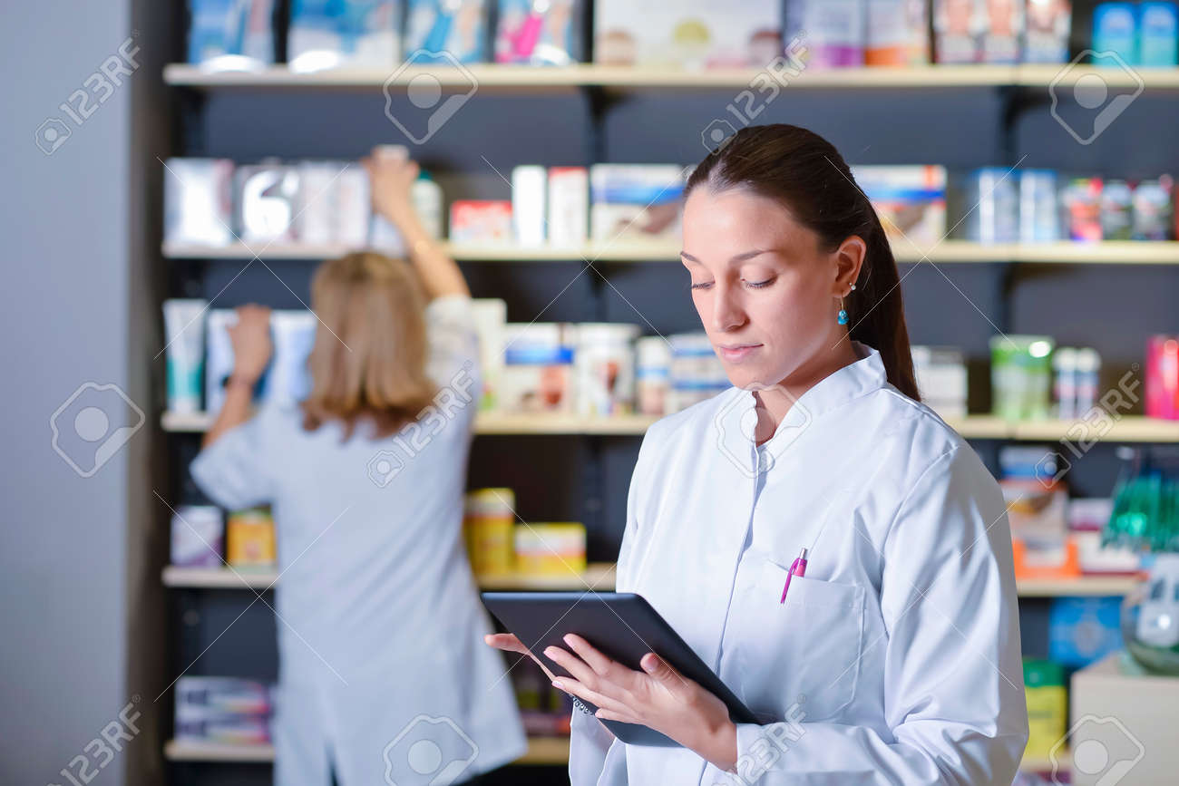 Young pharmacist standing next to medicine shelves, holding tablet - 135695220