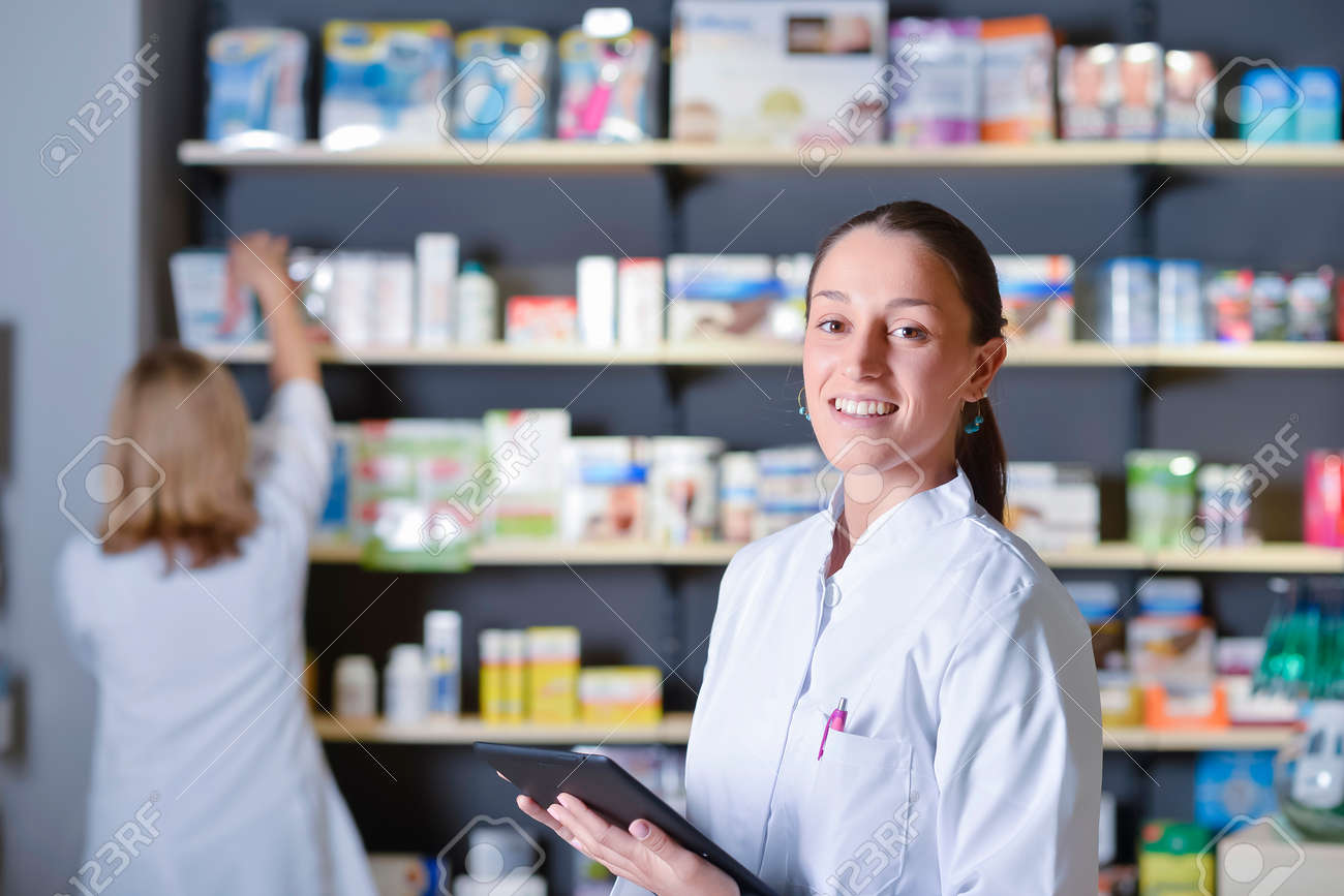 Young pharmacist standing next to medicine shelves, holding tablet - 135695221