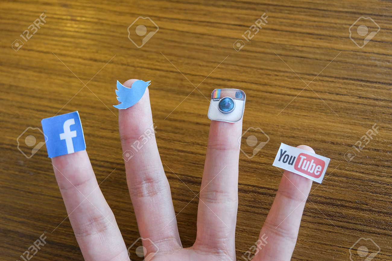 CHIANG MAI, THAILAND - SEPTEMBER 24, 2014: Social media brands printed on sticker and placed on human finger. Include Facebook, Twitter, Instagram and Youtube. - 32165923