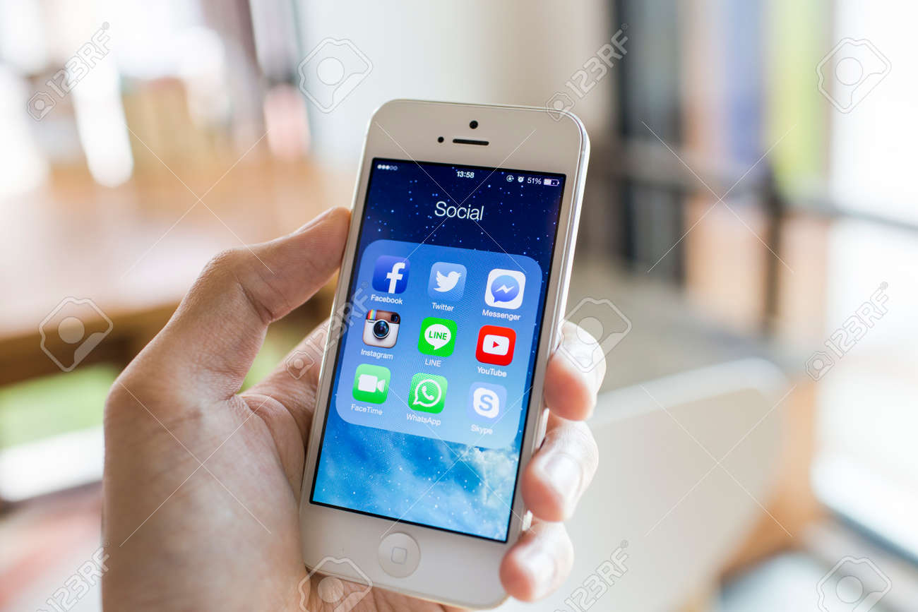 CHIANG MAI, THAILAND - SEPTEMBER 07, 2014: All of popular social media icons on smartphone device screen with hand holding on Apple iPhone 5. - 32165908