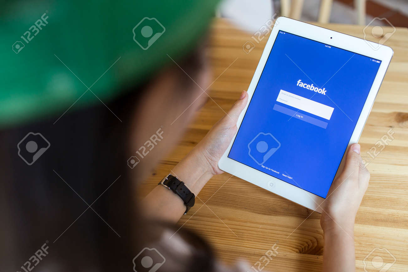 CHIANG MAI, THAILAND - SEPTEMBER 07, 2014: A girl trying to log in Facebook application using Apple iPad Air. Facebook is largest and most popular social networking site in the world. - 32165837
