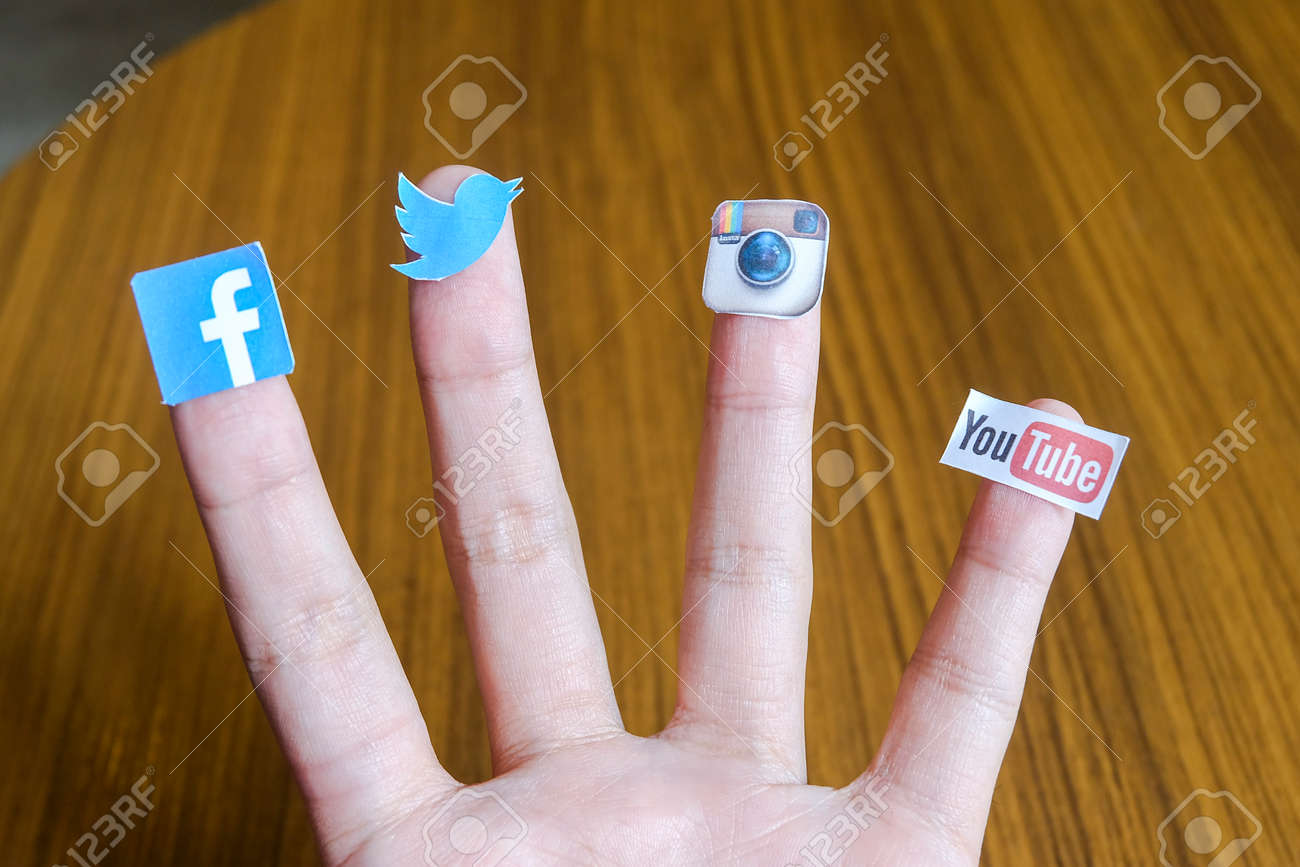 CHIANG MAI, THAILAND - SEPTEMBER 24, 2014: Social media brands printed on sticker and placed on human finger. Include Facebook, Twitter, Instagram and Youtube. - 36939534