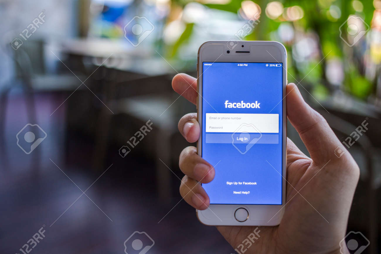 CHIANG MAI, THAILAND - JANUARY 02, 2015: A man trying to log in Facebook application using Apple iPhone 6. Facebook is largest and most popular social networking site in the world. - 37020018