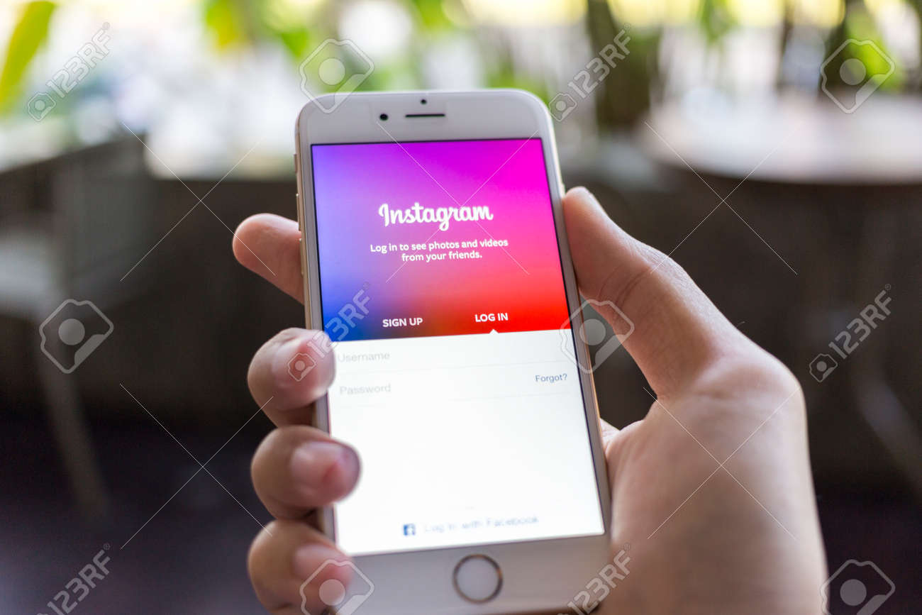 CHIANG MAI, THAILAND - JANUARY 02, 2015: A man trying to log in Instagram application using Apple iPhone 6. Instagram is largest and most popular photograph social networking site in the world. - 37020041