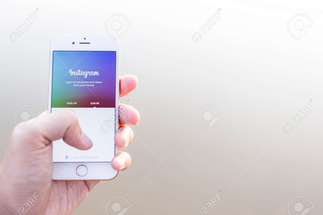 CHIANG MAI, THAILAND - JANUARY 02, 2015: A man trying to log in Instagram application using Apple iPhone 6. Instagram is largest and most popular photograph social networking site in the world. - 37020100