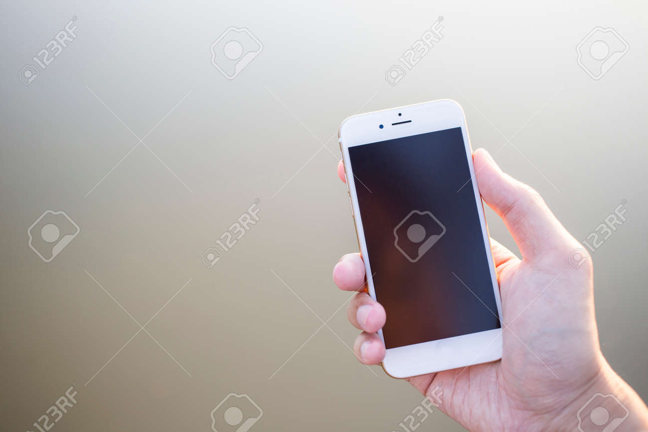 Man hand holding smartphone against on smooth background. - 37028116