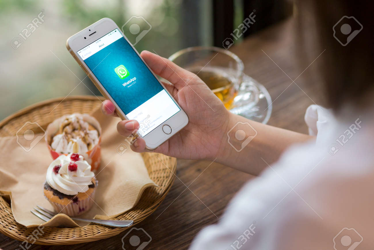 CHIANG MAI, THAILAND - JUNE 28, 2015: Woman hold iPhone 6 with social Internet service WhatsApp on the screen in coffee shop. iPhone 6 was created and developed by the Apple inc. - 43514615