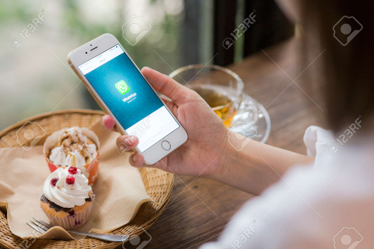 CHIANG MAI, THAILAND - JUNE 28, 2015: Woman hold iPhone 6 with social Internet service WhatsApp on the screen in coffee shop. iPhone 6 was created and developed by the Apple inc. - 43514665