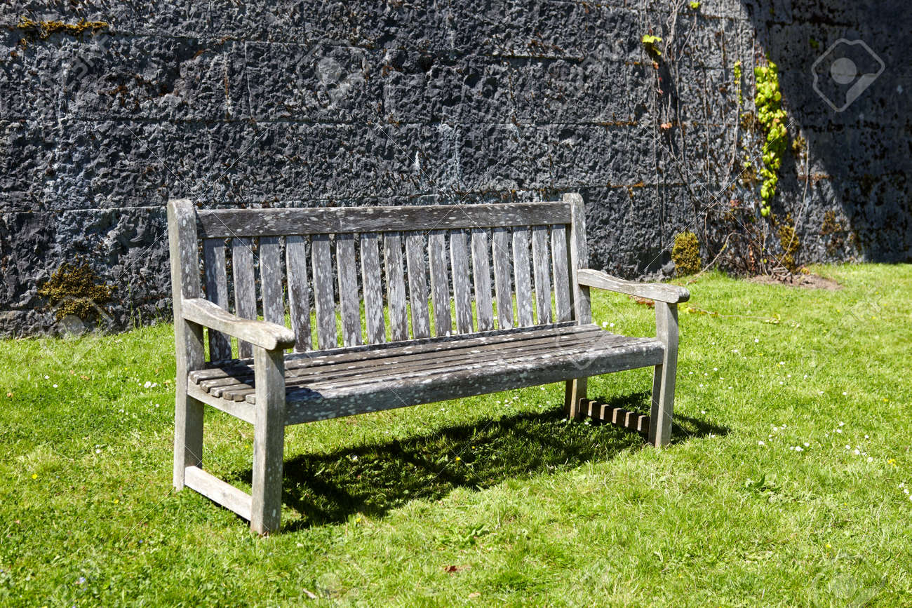 Vintage Wooden Garden Bench Against Stone Wall