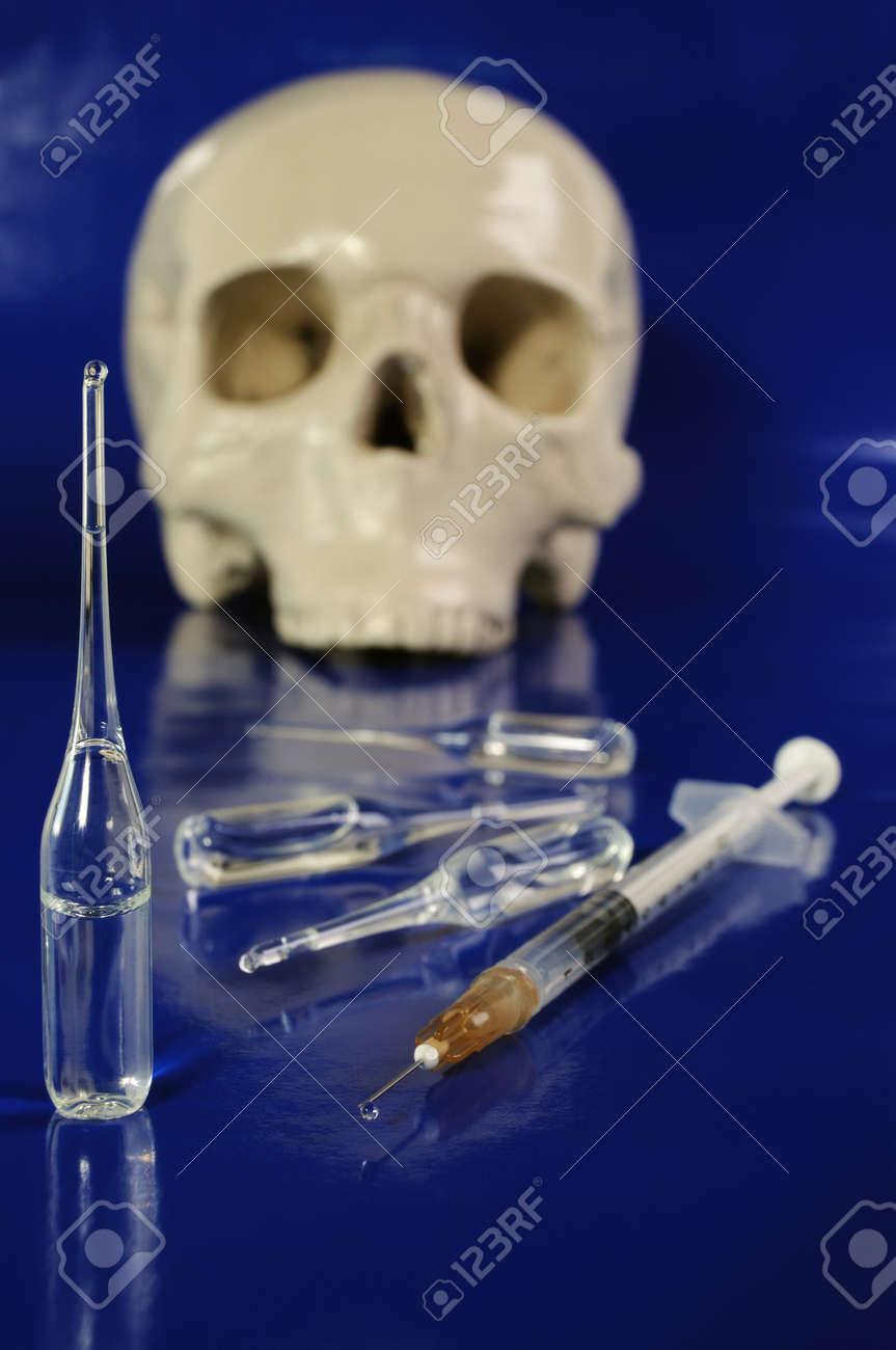 Medical phial, syringe and skull  against dark blue background Stock Photo - 6973188