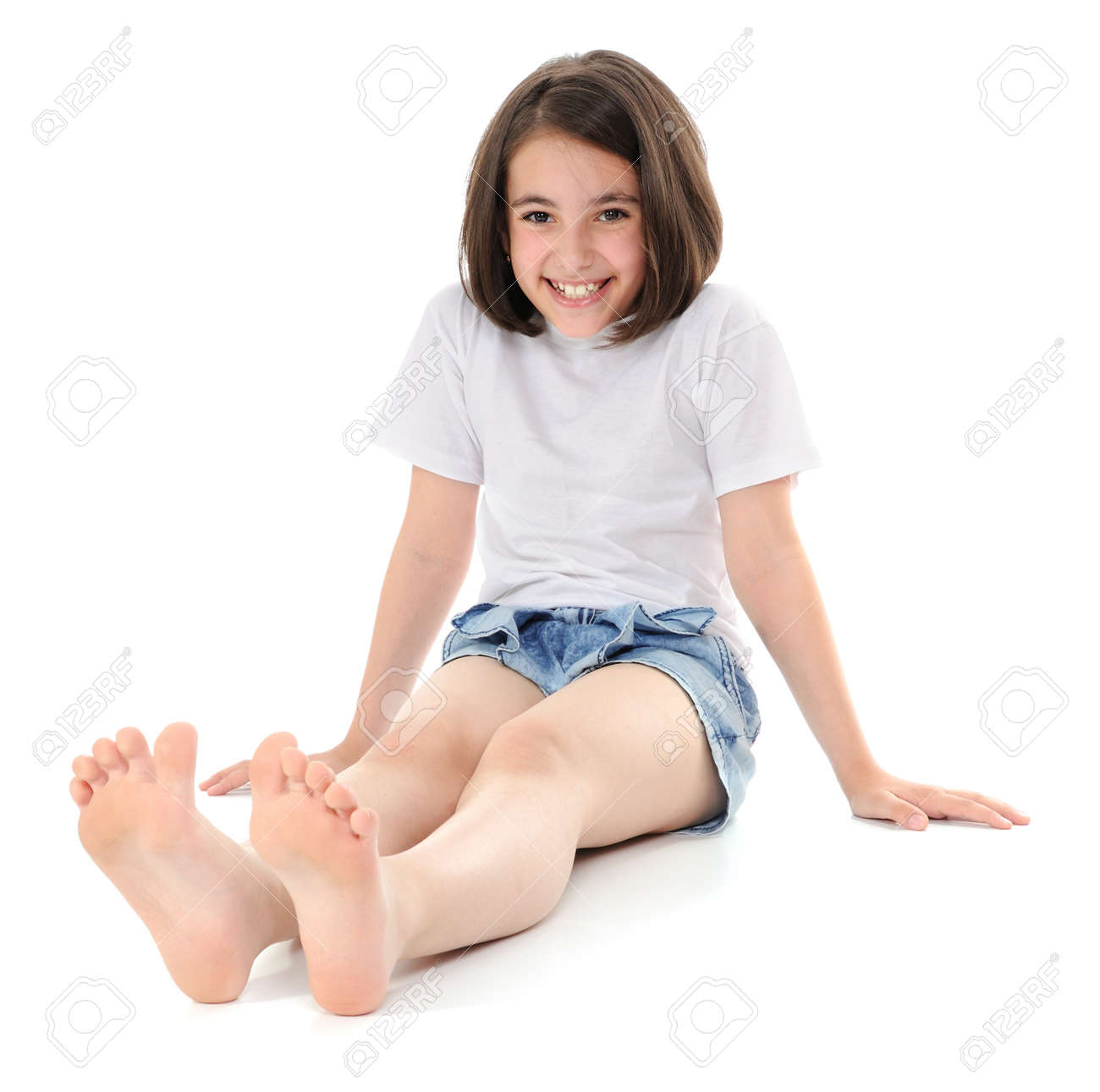 smiling girl sitting on a floor looking at camera stock photo