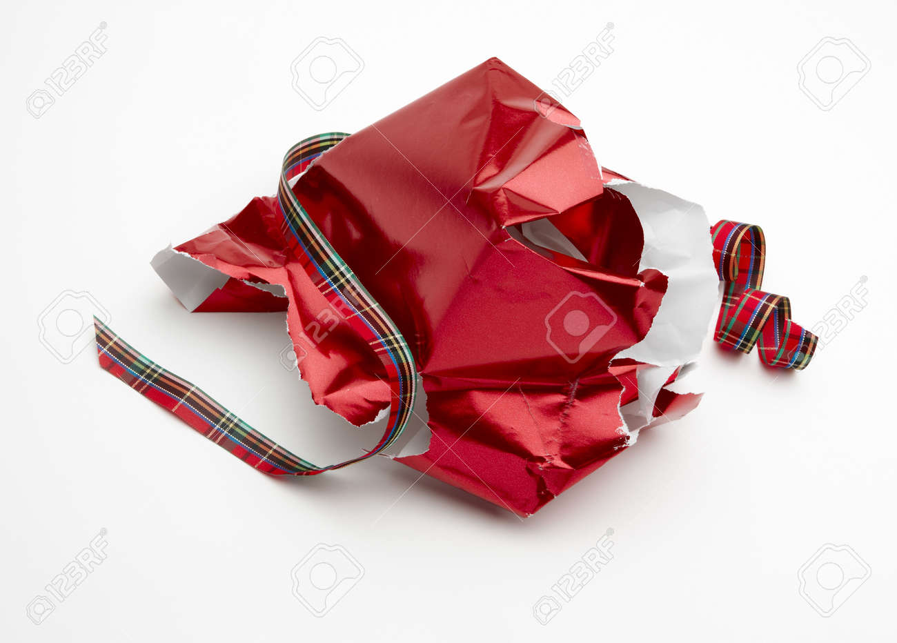 Torn christmas gift wrapper and ribbon shot on white background stock photo torn christmas gift wrapper and ribbon shot on white background with soft shadow and room for copy negle